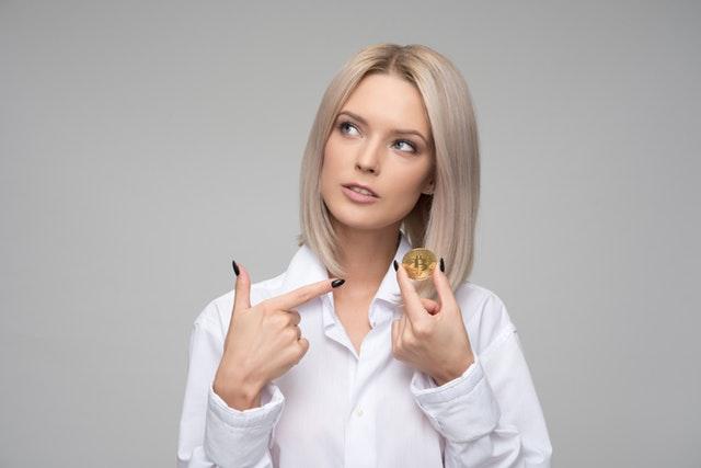 žena, která prstem ukazuje na Bitcoin.jpg